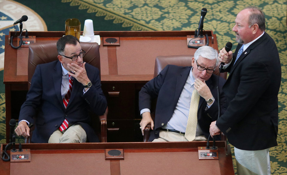 Photo -  State Rep. Kevin Wallace addresses the House on Saturday as Reps. Randy McDaniel and Weldon Watson listen during the special session at the Capitol. [Photo by Doug Hoke, The Oklahoman]