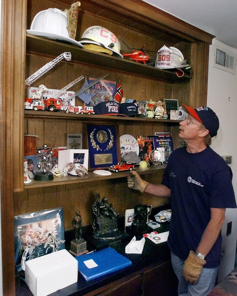 Tornado victims, damage: Assistant Fire Chief Jon Hansen in his house that was hit by the tornado. This bookcase contained his bombing mementos and was untouched. Goes with Robert Medley's Sunday story.