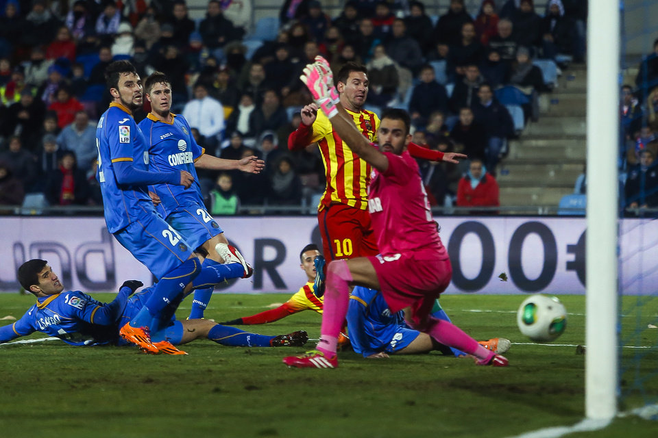 Photo - Barcelona's Lionel Messi, second right, scores his goal in between players  during a Spanish Copa del Rey match between FC Barcelona and Getafe at the Coliseum Alfonso Perez stadium in Madrid, Spain, Thursday, Jan. 16, 2014. (AP Photo/Andres Kudacki)