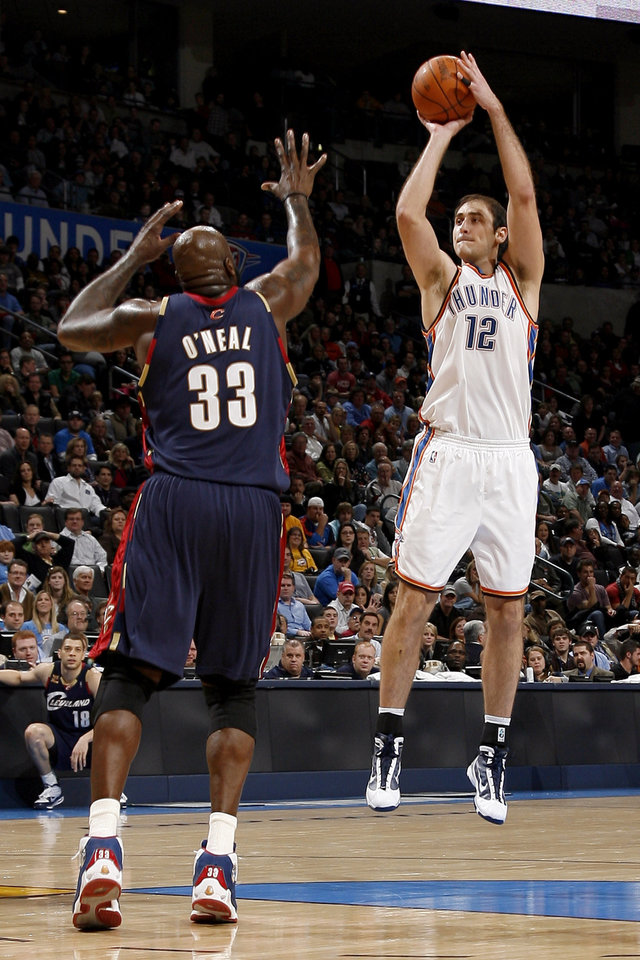 Photo - Oklahoma City's Nenad Krstic (12) shoots over Cleveland's Shaquille O'Neal (33) during the NBA game between the Oklahoma City Thunder and the Cleveland Cavaliers, Sunday, Dec. 13, 2009, at the Ford Center in Oklahoma City. Photo by Sarah Phipps, The Oklahoman
