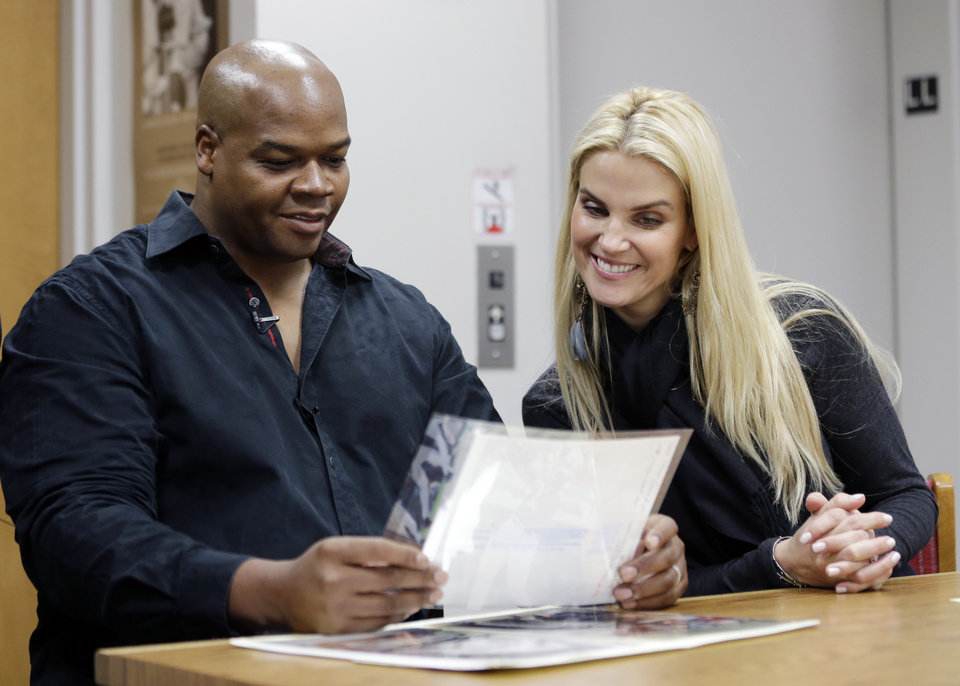 Photo - Former Chicago White Sox player Frank Thomas and wife Megan look at old photos of his playing days during an orientation visit at the Baseball Hall of Fame on Monday, March 3, 2014, in Cooperstown, N.Y. Thomas will be inducted to the hall in July. (AP Photo/Mike Groll)