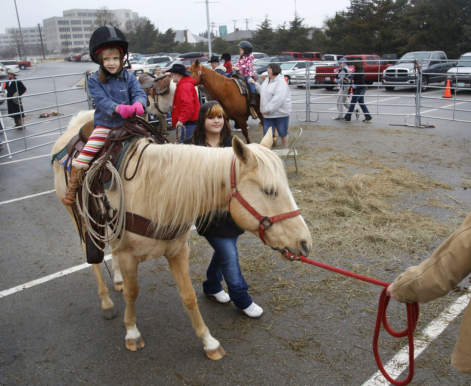 "A girl rides a pony around the pen. Children with their parents endured cold temperatures and intermittent rain to come to the grounds of the Oklahoma History Center on Saturday, March 23, 2013, to participate in the 3rd annual Cowboy Round-up,  billed to be a  ""rendezvous with adventure.""  Cowboys and chuck wagons were on hand to bring the cattle drive era to life for visitors of all ages. Special activities included pony rides, stick-horse races, roping demonstrations, branding,  a medicine man show, biscuits made from scratch and cooked in Dutch ovens, and a chance for children to make a braided rope they could take with them as a souvenir.  Youth were encouraged to dress the part as many did, wearing boots, vests, bandanas, chaps,and cowboy hats.    Photo by Jim Beckel, The Oklahoman"