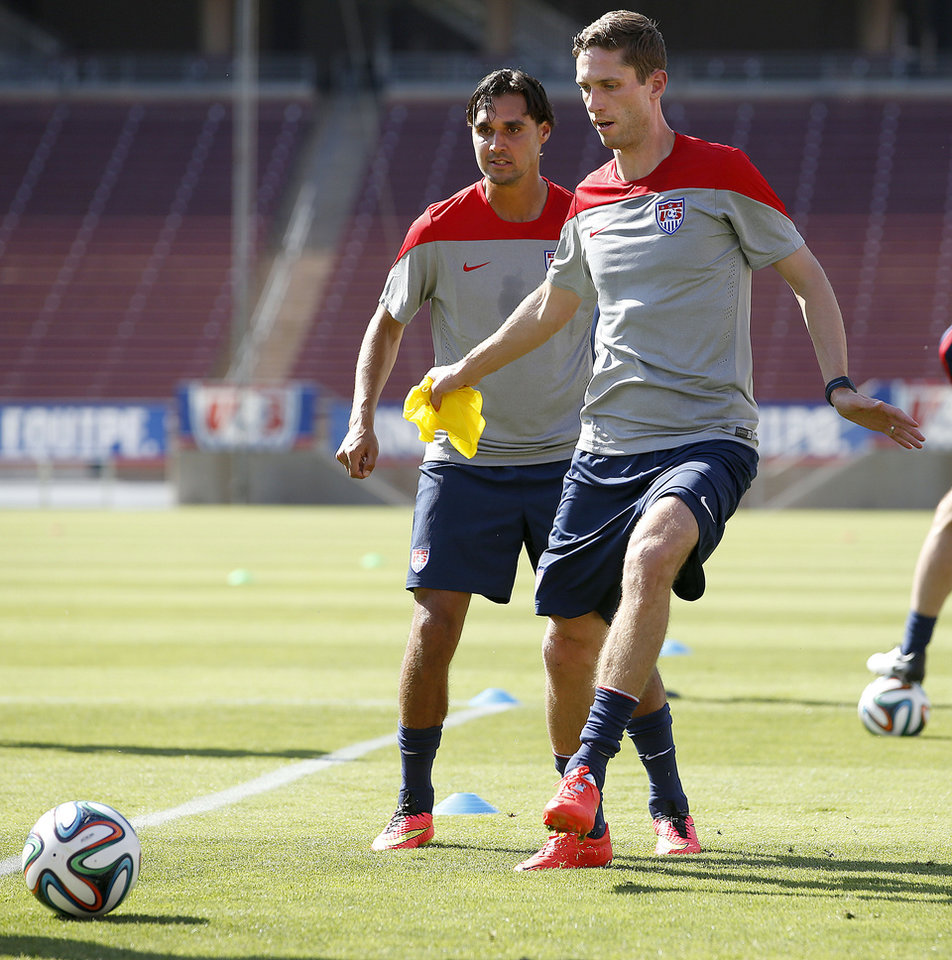Photo - United States' Clarence Goodson, right, controls the ball next to teammate Chris Wondolowski during a training session Wednesday, May 14, 2014, in Stanford, Calif. The team began a two-week training camp leading up to a May 27 exhibition with Azerbaijan at San Francisco's Candlestick Park. (AP Photo/Tony Avelar)