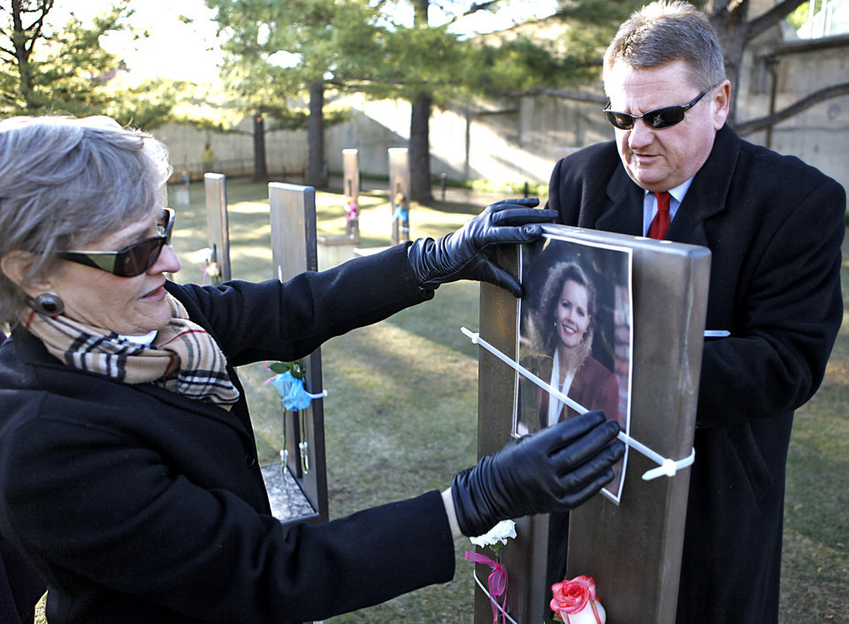 Photo - Cindy and Albert Ashwood place a before the 18th Anniversary Remembrance Ceremony at the Oklahoma City National Memorial and Museum, Friday, April 19, 2013. Photo By David McDaniel/The Oklahoman