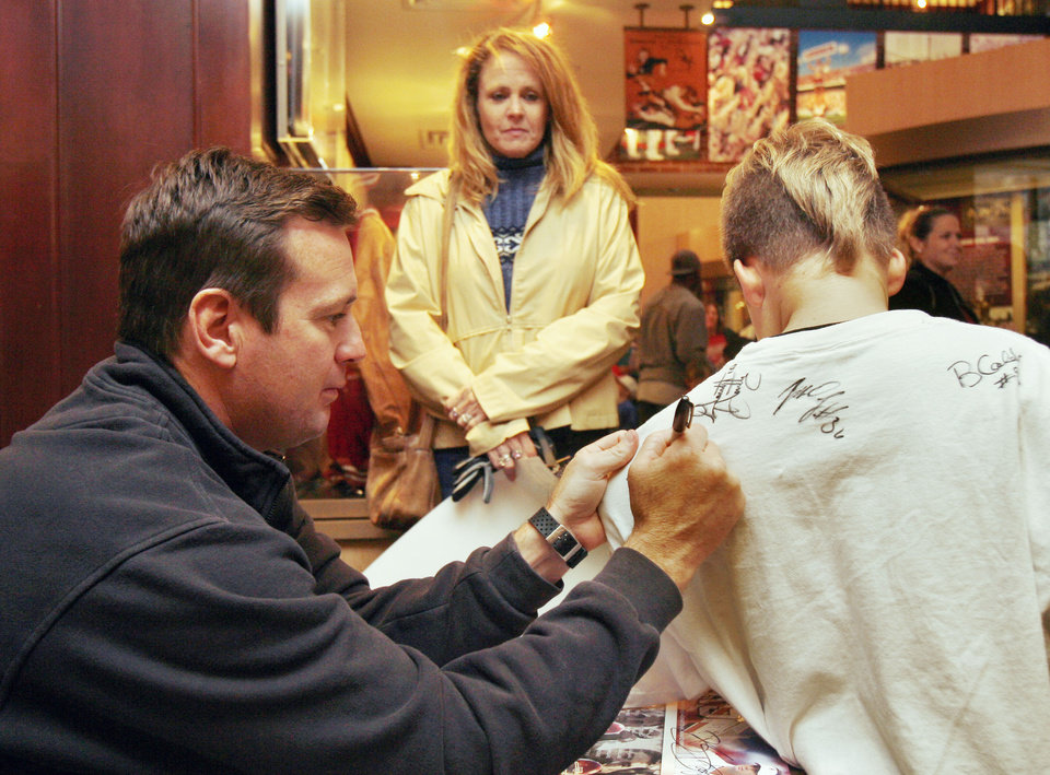 Photo - UNIVERSITY OF OKLAHOMA: OU Head Coach Bob Stoops signs his autograph for 8-year-old Rocky Frieburg and his mom Beth during an event sponsored by the Heupel Foundation which distributed food to families at the Switzer Center on the OU campus in Norman, Okla., Monday, November 13, 2006. Photo by Paul Hellstern / The Oklahoman. ORG XMIT: KOD