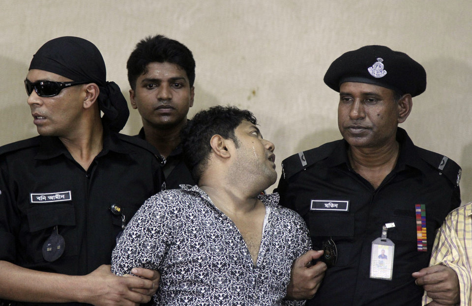 Photo - Mohammed Sohel Rana, center, the fugitive owner of an illegally-constructed building that collapsed last week in Bangladesh, reacts as he is produced before the media in Dhaka, Bangladesh, Sunday, April 28, 2013. Rana was arrested near the land border in Benapole in western Bangladesh, just as he was about to flee into India's West Bengal state, said Jahangir Kabir Nanak, junior minister for local government. (AP Photo/Palash Khan)