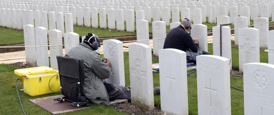 Photo - Two engravers work on re-engraving the headstones of WWI soldiers at Tyne Cot cemetery in Zonnebeke, Belgium on Monday, April 15, 2013. With nearly 12,000 graves the cemetery is the largest Commonwealth war cemetery in the world in terms of burials. Commonwealth cemeteries around the world are currently being renovated in preparation for centenary events which begin in 2014. (AP Photo/Virginia Mayo)