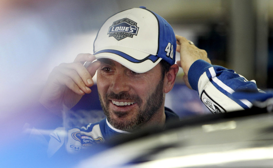 Photo - NASCAR driver Jimmie Johnson smiles during a break in practice for Sunday's Sprint Cup series auto race at New Hampshire Motor Speedway, Friday, July 11, 2014, in Loudon, N.H. (AP Photo/jim cole)