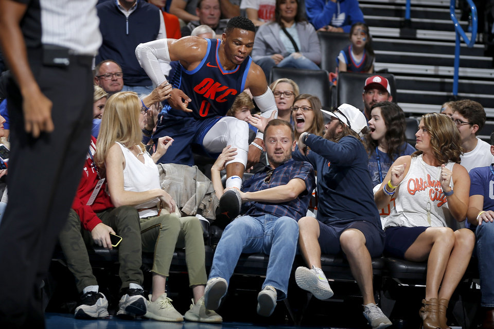 Photo - Oklahoma City's Russell Westbrook (0) climbs out of the crowd after diving for the ball during an NBA basketball game between the Oklahoma City Thunder and the Sacramento Kings at Chesapeake Energy Arena in Oklahoma City, Sunday, Oct. 21, 2018. Photo by Bryan Terry, The Oklahoman