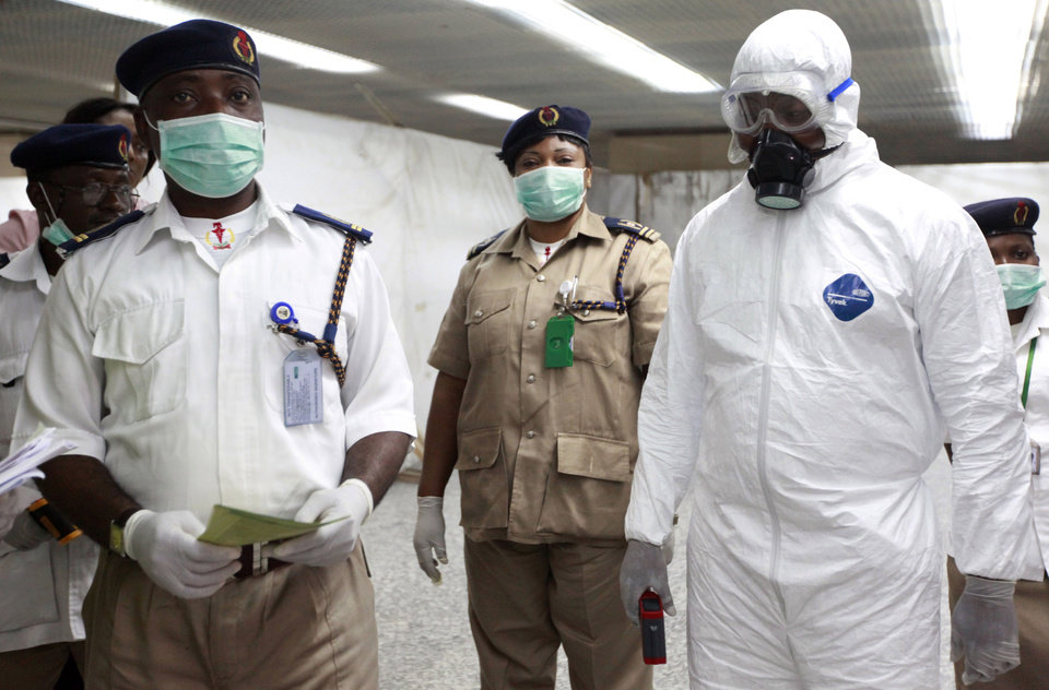 Photo - Nigerian health officials wait to screen passengers at the arrivals hall of Murtala Muhammed International Airport in Lagos, Nigeria, Monday, Aug. 4, 2014. Nigerian authorities on Monday confirmed a second case of Ebola in Africa's most populous country, an alarming setback as officials across the region battle to stop the spread of a disease that has killed more than 700 people. (AP Photo/Sunday Alamba)