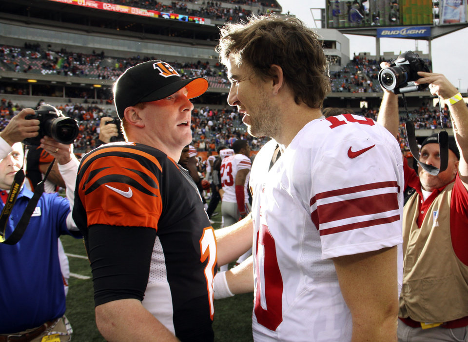 Photo -   Cincinnati Bengals quarterback Andy Dalton (14) meets with New York Giants quarterback Eli Manning (10) after the Bengals' 31-13 win in an NFL football game, Sunday, Nov. 11, 2012, in Cincinnati. (AP Photo/Tom Uhlman)