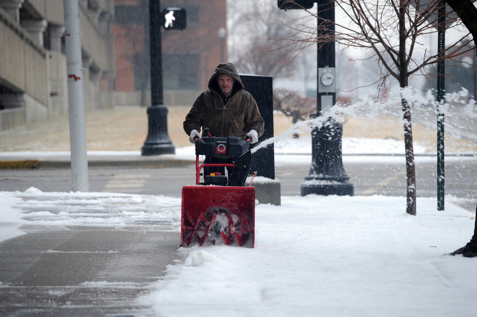 Photo - Dean Stratton works to remove snow on the sidewalk around Fifth Third Bank while working for VIOX Services in Evansville Evansville, Ind., Tuesday, Feb. 4, 2014.  A Winter Storm Warning was issued Tuesday as a mixture of snow, sleet and rain continued into the evening with temperatures around 30 degrees. (AP Photo/The Evansville Courier & Press, Jason Clark)