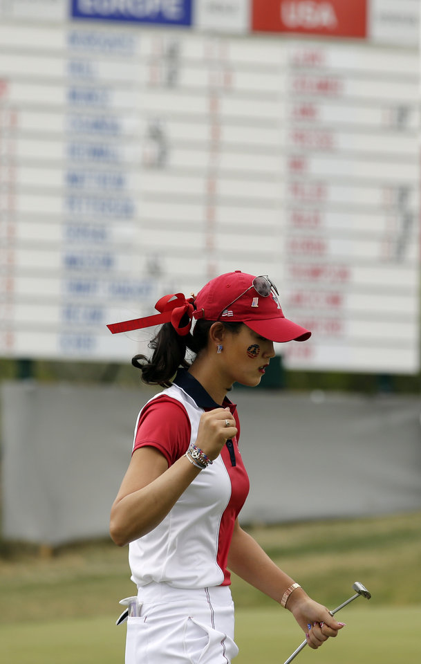 Photo - United States' Michelle Wie pumps her fist after winning the eighth hole during her singles match against Europe's Caroline Hedwall, from Sweden, at the Solheim Cup golf tournament on Sunday, Aug. 18, 2013, in Parker, Colo. (AP Photo/Chris Carlson)