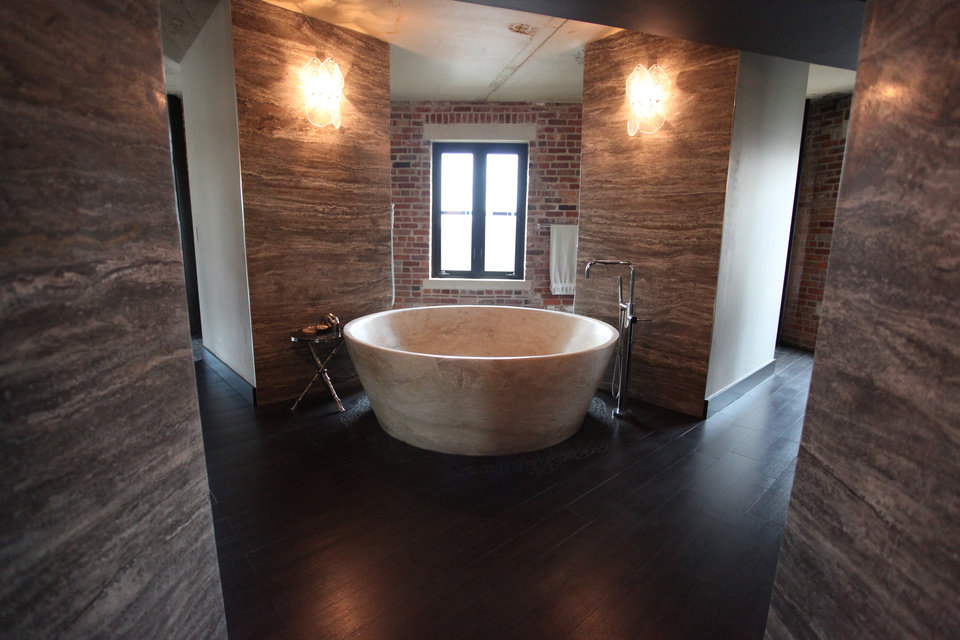Photo -  A massive tub is the centerpiece of the master bathroom, a stark space that includes contrasting wood, stone and brick.