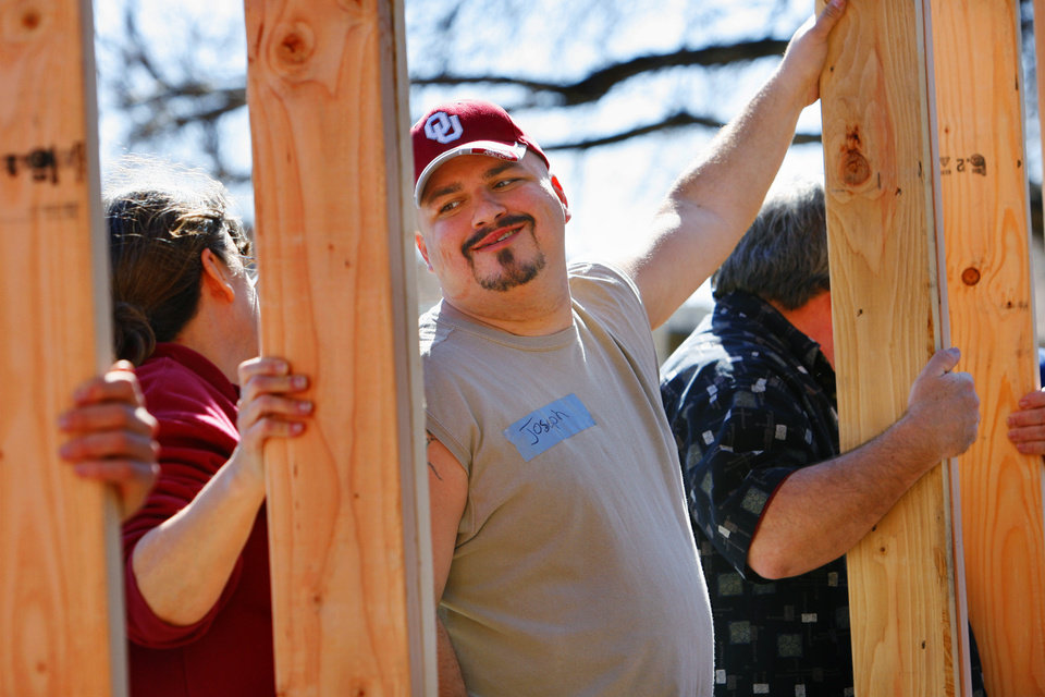 Photo - Future home owner Joseph Johnson smiles at his mother Diane Johnson as the first wall is raised as volunteers and Habitat for Humanity staff work on his home at 313 W Himes in Norman, Okla. on Friday, Feb. 6, 2009.   Photo by Steve Sisney, The Oklahoman