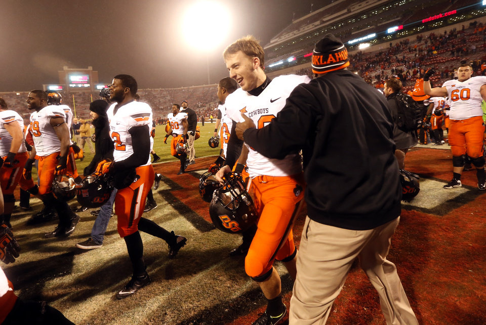 Photo - Oklahoma State's Ben Grogan (19) runs off the field following the Bedlam college football game between the University of Oklahoma Sooners (OU) and the Oklahoma State Cowboys (OSU) at Gaylord Family-Oklahoma Memorial Stadium in Norman, Okla., Saturday, Dec. 6, 2014. Photo by Sarah Phipps, The Oklahoman