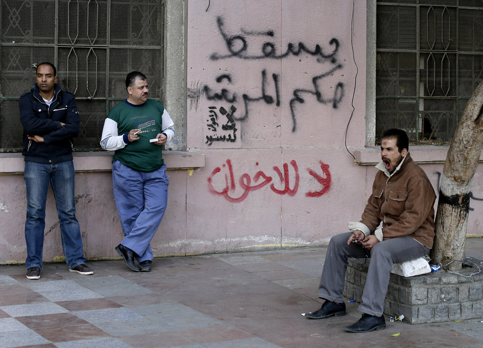 Egyptian men stand near Arabic writing on a wall in Arabic that reads,