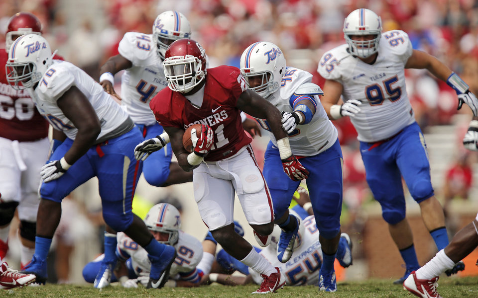 Oklahoma's Keith Ford (21) runs pas the Tulsa defense during the college football game between the University of Oklahoma Sooners (OU) and the University of Tulsa Hurricanes (TU) at the Gaylord-Family Oklahoma Memorial Stadium on Saturday, Sept. 14, 2013 in Norman, Okla.  Photo by Chris Landsberger, The Oklahoman