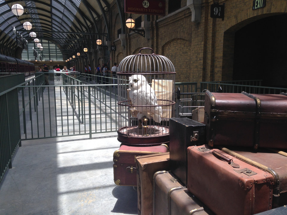 Photo - An owl sits amid baggage inside King's Cross Station, part of The Wizarding World of Harry Potter-Diagon Alley, a new park opening July 8 at Universal Orlando Resort in Florida, on Thursday, June 19, 2014. A train ride connects King's Cross with another themed station on the other side of the Universal Orlando theme park where Universal's original Harry Potter attraction opened in 2010. The parks are richly detailed, with settings and characters inspired by the Harry Potter series of books and films. (AP Photo/Tamara Lush)