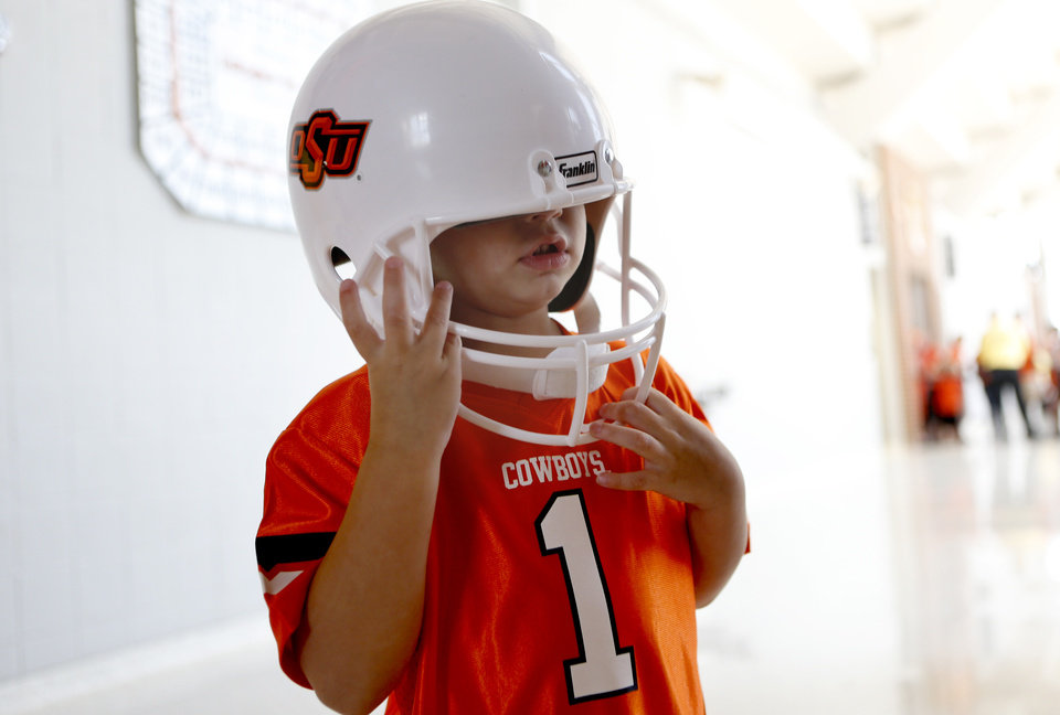 Photo - Fan Tayten Bruce, 3, wears a OSU helmet as he waits to greet players during Oklahoma State's Fan Appreciation Day at Gallagher-Iba Arena in Stillwater, Okla., Saturday, Aug. 4, 2012. Photo by Sarah Phipps, The Oklahoman