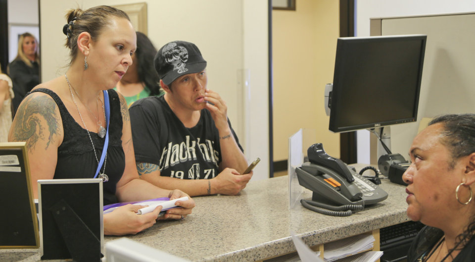 Photo - Rose Southall, left, and her partner, Brandi Mahan get the word from Senior Assessment Clerk Jennifer Samuela in the San Diego County marriage license office that ceremonies to get married are booked for the week in San Diego, Monday, July 1, 2013. The couple have been together for 10 and-half-years and said they can wait.   (AP Photo/Lenny Ignelzi)