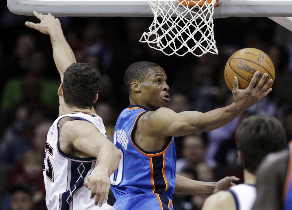 Photo - Oklahoma City Thunder's Russell Westbrook takes a shot past New Jersey Nets' Kris Humphries during the first quarter of an NBA basketball game in Newark, N.J., Saturday, Jan. 21, 2012. (AP Photo/Mel Evans) ORG XMIT: NJME118