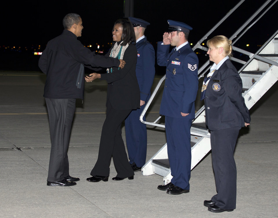 President Barack Obama greets first lady Michelle Obama on the tarmac as she arrives at Des Moines International Airport on Air Force One, Monday, Nov. 5, 2012, in Des Moines, Iowa, en route to a campaign event. (AP Photo/Carolyn Kaster)