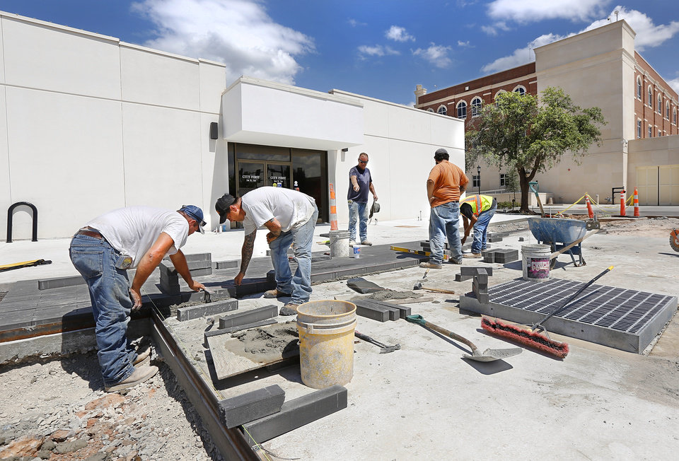 Photo -  A crew from Rudy Construction Co. works on the parking lot, sidewalks and entrance on the south side of Edmond's city hall at Second Street and Littler Avenue. [STAFF PHOTO BY JIM BECKEL, THE OKLAHOMAN]