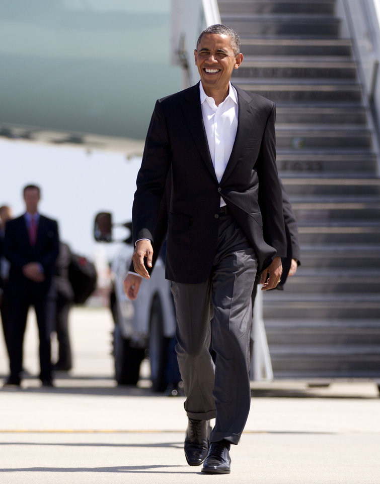 Photo -   President Barack Obama walks to greet people waiting for him on the tarmac as he arrives at O'Hare International Airport on Air Force One, Saturday, Aug. 11, 2012, in Chicago. (AP Photo/Carolyn Kaster)