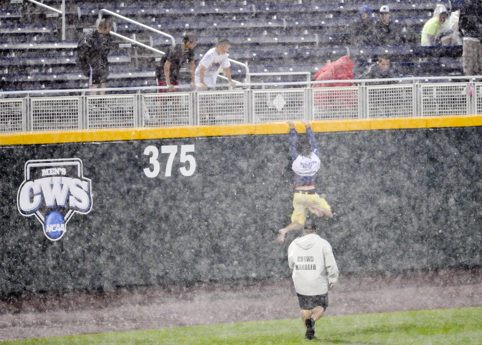 Photo -   A fan tries to escape from security up the outfield wall on Wednesday June 20, 2012, while waiting for the rain to pass at the NCAA College World Series elimination game between Kent State and South Carolina in Omaha, Neb. (AP Photo/Dave Weaver)