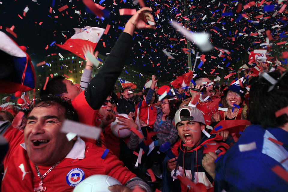 Photo - In this Friday, June 13, 2014 photo, soccer fans cheer as they watch Chile's Alexis Sanchez score the first goal of the World Cup match between Chile and Australia, via a live broadcast on a giant screen in front of La Moneda presidential palace, in Santiago, Chile. Sanchez produced a dynamic performance to lead Chile to a 3-1 win over Australia at the Arena Pantanal in Cuiaba, Brazil. (AP Photo/Luis Hidalgo)