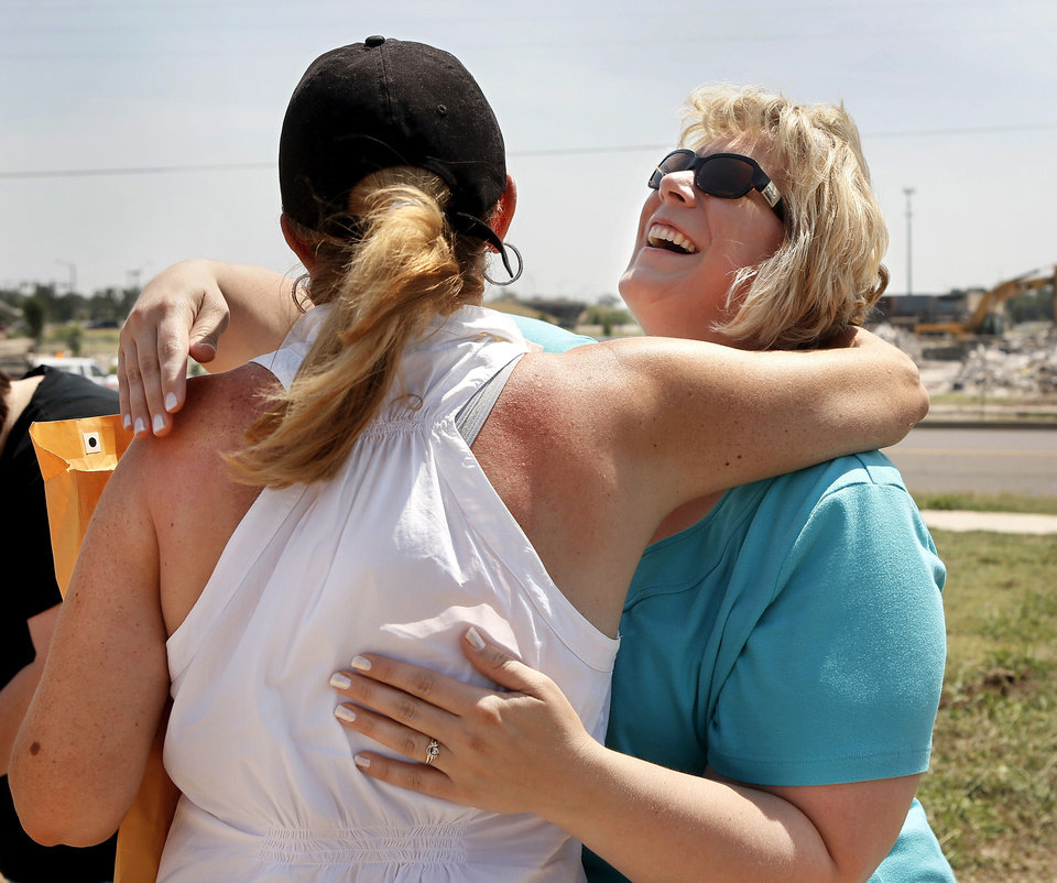 Amber Kriesel laughs after hugging television reporter Rebecca Cooper who holds an envelope containing cards and letters recovered from the Kriesel home after the tornado. Amber and Nathan Kriesel and their  three daughters survived the May 20 tornado, but their home at 601 SW 6 in Moore, and most of their possessions, were destroyed or scattered with the winds.  On Saturday, July 13, 2013, the couple brought their daughters to the site where their home once stood.  Nothing remains except dirt and sand. The foundation, driveway and sidewalks are piled about five-feet high next to the curb on 6th Street. Their neighborhood is practically.  Rebecca Cooper, a  reporter from a Washington D.C. television,  station met the Kriesel family   in their former yard to return to them a large manila envelope filled with  sentimental items, including family letters and cards,  and daughter Zoe's artwork, that had been salvaged from the ruins in the days after the twister demolished their home.  Nathan and Amber expressed  gratitude for  special keepsakes  that have been returned in the days and weeks following the storm -- Amber's locket, Nathan's high school soccer jacket and today,  the family's letters and cards' dating back decades, from parents, loved ones, friends and grandparents who are now deceased.     Photo  by Jim Beckel, The Oklahoman.