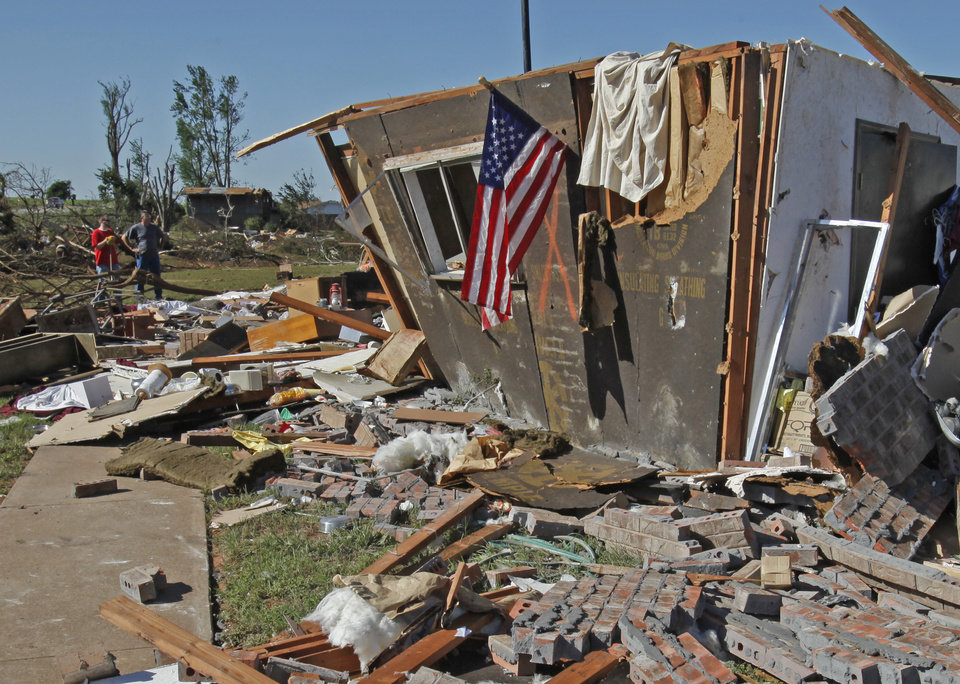 Photo - Louise McDaniel's home has an American Flag at the front as residents cleanup following Tuesday's deadly tornado  on Wednesday, May 25, 2011, in Chickasha, Okla.  Louise was with her hospitalized son Ronnie McDaniel in Oklahoma City when the tornado destroyed her home.  Louise McDaniel saw the destruction and recognized her yard from aerial television coverage. Photo by Steve Sisney, The Oklahoman