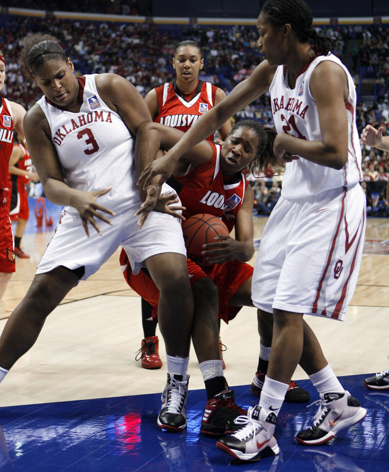 Photo - Courtney Paris and Amanda Thompson combine to block a shot by Keishia Hines in the first half as the University of Oklahoma plays Louisville at the 2009 NCAA women's basketball tournament Final Four in the Scottrade Center in Saint Louis, Missouri on Sunday, April 5, 2009. Photo by Steve Sisney, The Oklahoman
