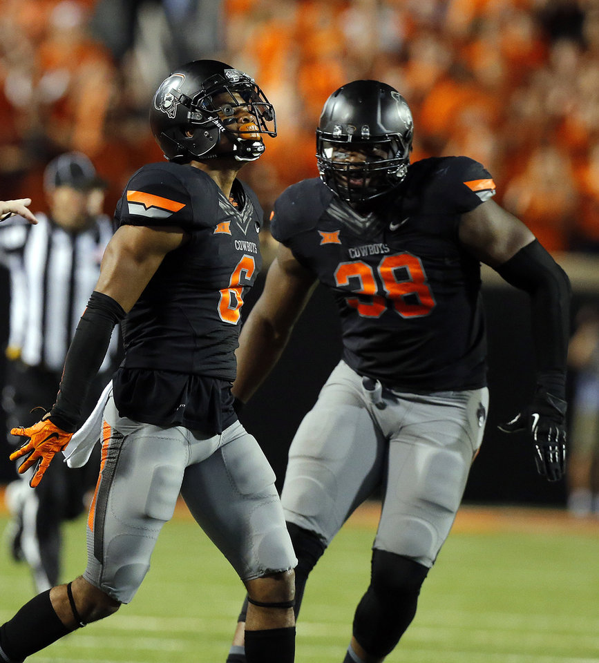 Photo - Oklahoma State's Ashton Lampkin (6) and Emmanuel Ogbah (38) celebrate a defensive play during the college football game between the Oklahoma State Cowboys (OSU) and the Central Arkansas Bears at Boone Pickens Stadium in Stillwater, Okla., Saturday, Sept. 12, 2015. Photo by Sarah Phipps, The Oklahoman