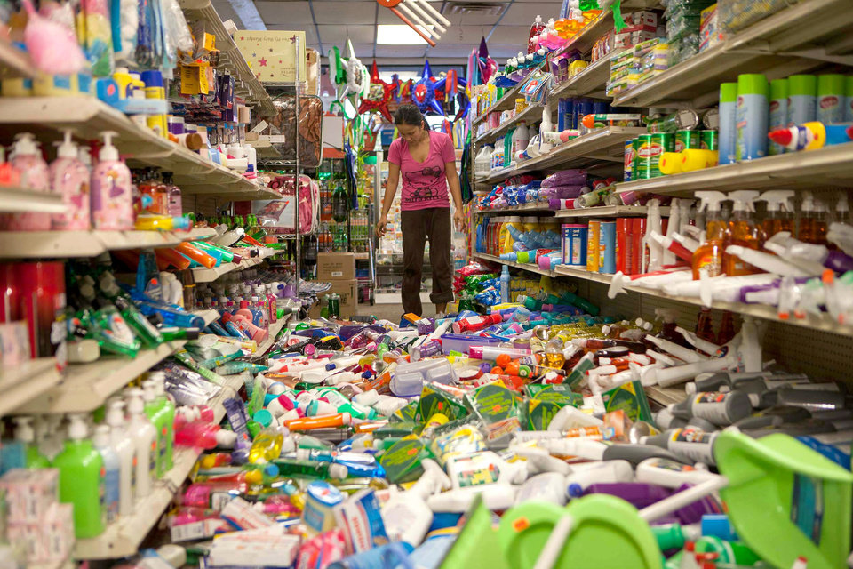 Nina Quidit cleans up the Dollar Plus and Party Supplies Store in American Canyon Calif. after an earthquake on Sunday Aug. 24, 2014. Quidit and her husband were woken up in the early morning hours by the store\'s alarm company and immediately drove in to begin clean up. The 6.0-magnitude quake caused six significant fires, including at four mobile homes, Napa Division Fire Chief Darren Drake said. (AP Photo/Alex Washburn)