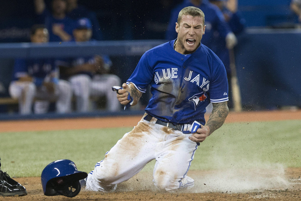 Photo - Toronto Blue Jays Brett Lawrie reacts at home plate after scoring on a single by Melky Cabrera off New York Yankees pitcher David Phelps during sixth inning MLB American League baseball action in Toronto on Sunday April 21, 2013. (AP Photo/THE CANADIAN PRESS,Chris Young)