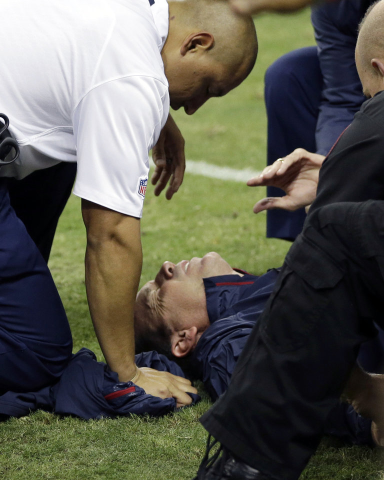 Photo - Houston Texans head coach Gary Kubiak, center, is helped after he collapsed on the field during the second quarter of an NFL football game against the Indianapolis Colts, Sunday, Nov. 3, 2013, in Houston. (AP Photo/David J. Phillip)