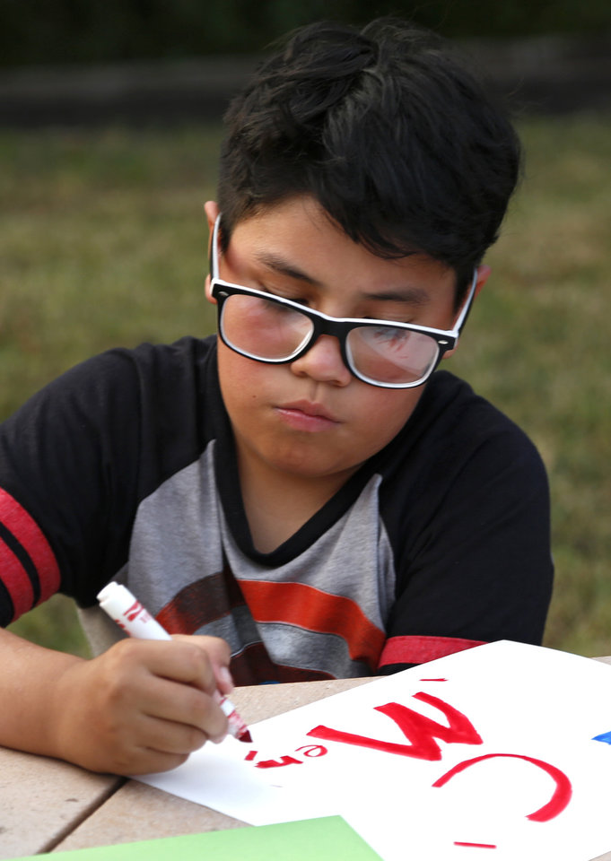 Photo -  Adrian, 10, makes a card during an arts and crafts time. [Photo by Kurt Steiss, The Oklahoman]