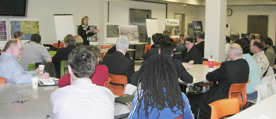 Photo - Robbie Kienzle, standing, an urban redevelopment specialist, addresses filmmakers, developers, property owners and others interested in reviving the old Film Row district at this 2006 meeting.  Steve Lackmeyer