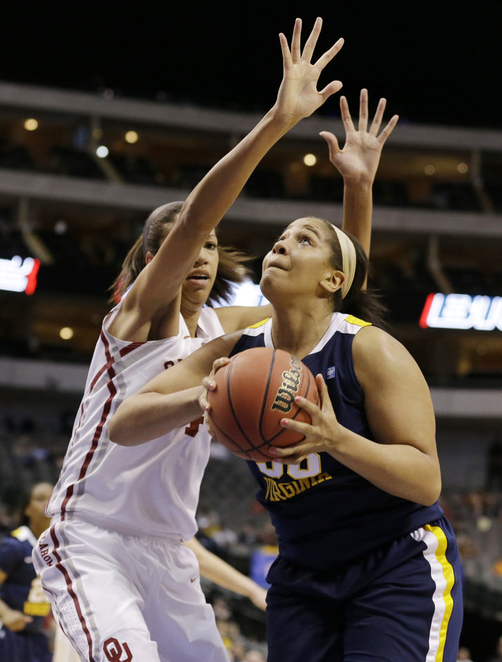 Photo - Oklahoma's Nicole Griffin, left, defends as West Virginia' Ayana Dunning, right, prepares to take a shot in the first half of an NCAA college basketball game in the Big 12 women's tournament Saturday, March 9, 2013, in Dallas. (AP Photo/Tony Gutierrez)
