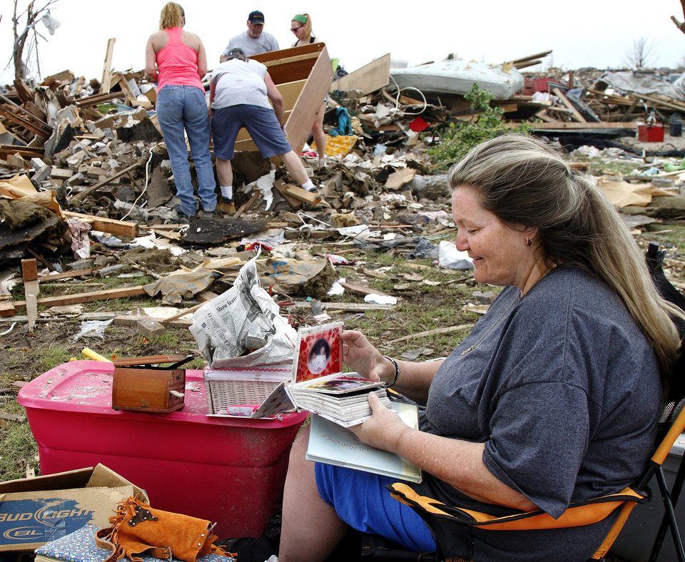 "Trina Minnick smiles as she flips through the pages of her child's photo album that was stored in a plastic tub. Minutes before, volunteer Darryl Gellenbeck had discovered the tub in the rubble of Minnick's home at 936 SW 15. Volunteers, including Gellenbeck's girlfriend and her mother, continue searching through Minnick's destroyed home. Minnick said, ""we're not moving back."" Volunteers from various parts of the country joined Oklahomans in assisting residents on Saturday,  May 25, 2013, doing whatever was needed to remove debris and salvage items from this neighborhood east of Santa Fe, north of SW 19 Street.  An EF5 tornado leveled many neighborhoods in Moore and southwest Oklahoma City last Monday.   Photo  by Jim Beckel, The Oklahoman."
