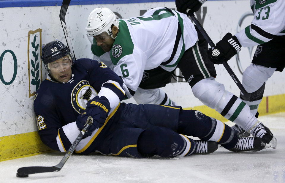 Photo - St. Louis Blues' Chris Porter, left, reaches for a loose puck as he is pushed down by Dallas Stars' Trevor Daley during the second period of an NHL hockey game Saturday, March 29, 2014, in St. Louis. (AP Photo/Jeff Roberson)