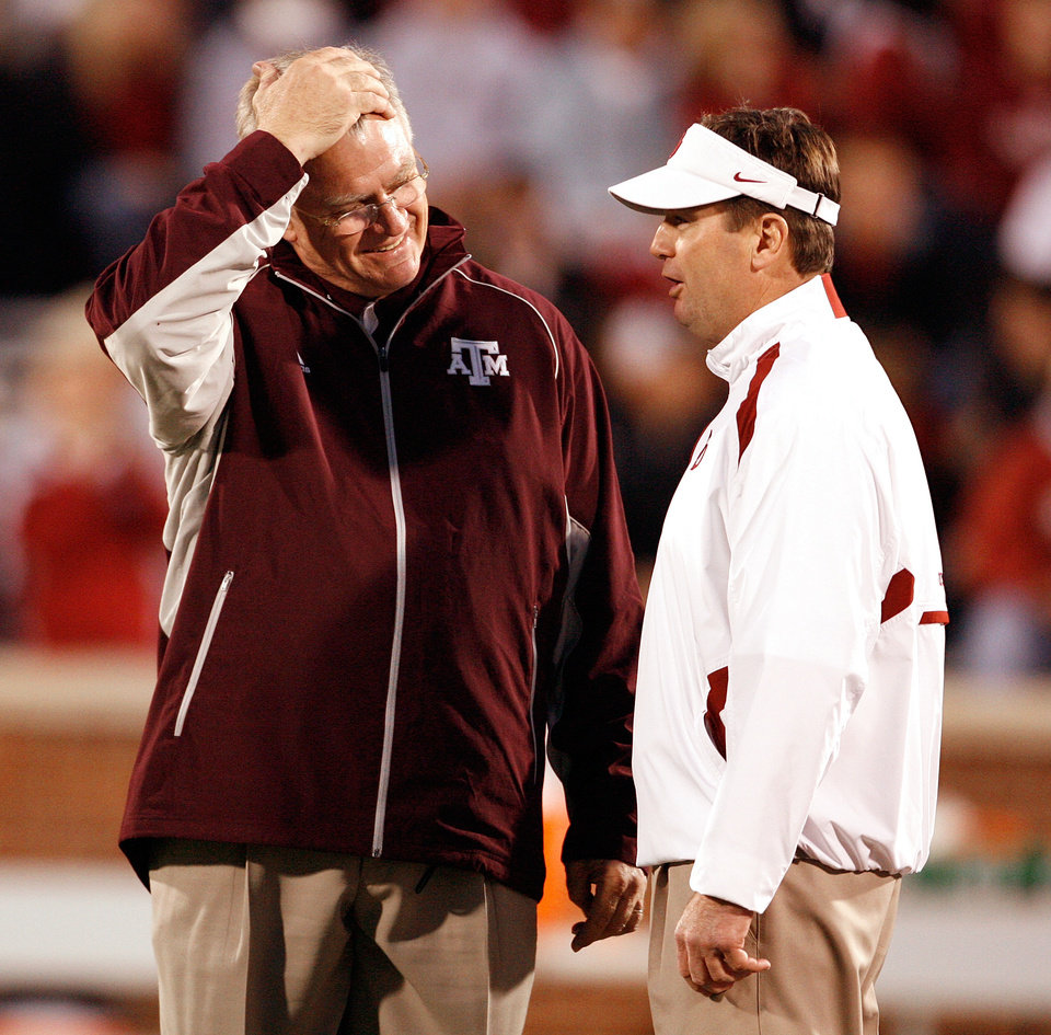 Photo - Head coaches Mike Sherman and Bob Stoops meet before the college football game between the University of Oklahoma Sooners (OU) and the Texas A&M at the Gaylord Familiy-Oklahoma Memorial Stadium on Saturday, Oct. 31, 2009, in Norman, Okla.