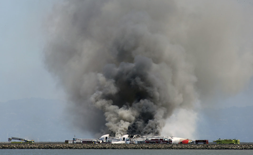 Photo - Smokes rises from Asiana Flight 214 after it crashed at San Francisco International Airport in San Francisco, Saturday, July 6, 2013. (AP Photo/Bay Area News Group, John Green)