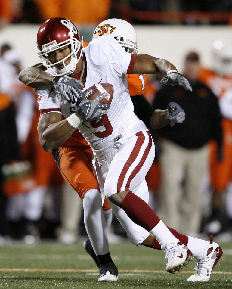 Photo - Juaquin Iglesias fights with Jacob Lacey on his back during the first half of the college football game between the University of Oklahoma Sooners (OU) and Oklahoma State University Cowboys (OSU) at Boone Pickens Stadium on Saturday, Nov. 29, 2008, in Stillwater, Okla. STAFF PHOTO BY BRYAN TERRY
