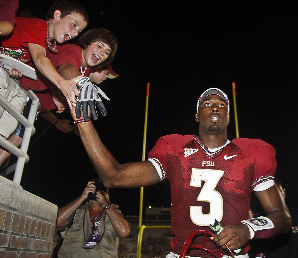 Photo - Florida State quarterback E.J. Manuel (3) gives away his glove to a fan as he leaves after an NCAA college football game against Charleston Southern on Saturday, Sept. 10, 2011, in Tallahassee, Fla. FSU won 62-10. (AP Photo/Phil Sears) ORG XMIT: FLPS111