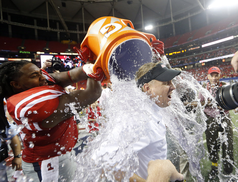 Photo - Mississippi coach Hugh Freeze gets dunked by Mississippi offensive linesman Justin Bell after Mississippi defeated Boise State 35-13 in an NCAA college football game Thursday, Aug. 28, 2014, in Atlanta. (AP Photo/John Bazemore)