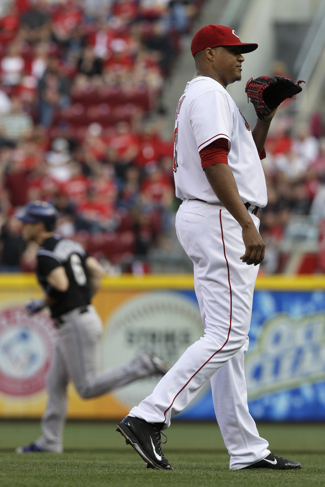 Photo - Cincinnati Reds starting pitcher Alfredo Simon, right, stands on the mound after giving up a home run to Colorado Rockies' Corey Dickerson (6) in the first inning of a baseball game on Saturday, May 10, 2014, in Cincinnati. (AP Photo/Al Behrman)