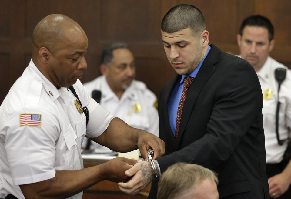 Photo - A court officer, left, removes handcuffs from former New England Patriots football player AaronHernandez, right, during a hearing in Suffolk Superior Court, Tuesday, June 24, 2014, in Boston. Prosecutors allege that Hernandez ambushed and shot to death two men, Daniel de Abreu and Safiro Furtado, in 2012 after a chance encounter inside a Boston nightclub. Hernandez has pleaded not guilty. (AP Photo/Steven Senne, Pool)
